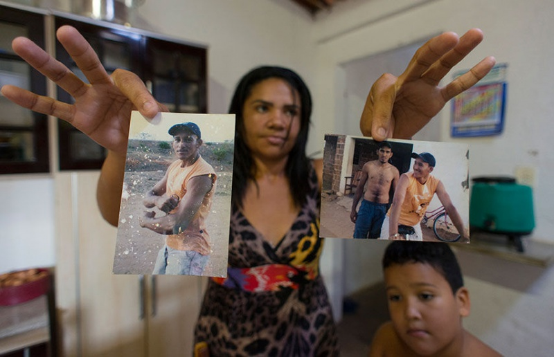 Gerlene Santos holds photos of her late husband, Vanderlei Matos da Silva (left), who died after exposure to pesticides in his job at a pineapple plantation run by Fresh Del Monte. A court recently upheld a $110,000 award in her favor over his death. REUTERS/Davi Pinheiro
